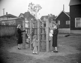 [Women from the Junior League helping children climb some playground equipment]