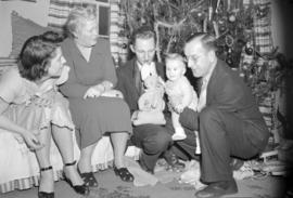[Thornton baby receiving a stuffed rabbit from relatives at Christmas]