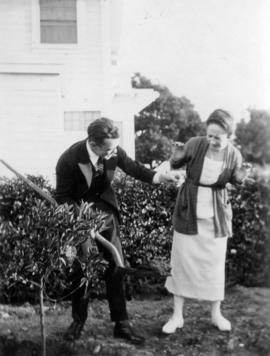 [Ted Taylor and unidentified woman in yard]