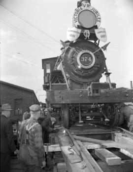 [Engine 374 being secured onto the back of a truck for transport]