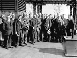 [Group portrait showing Mayor L.D. Taylor standing with a large group of men in an outdoor courty...