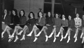 [Women wtih skates sitting on the barrier at the side of the new ice rink]