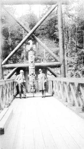 [L.D. Taylor and unidentified man in front of totem pole at the Capilano Suspension Bridge]