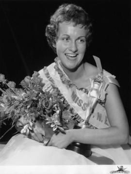 Portrait of Sharon Durham, Miss P.N.E. 1958, posing with flowers and trophy