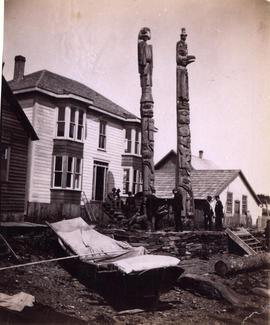 [House and totem poles]