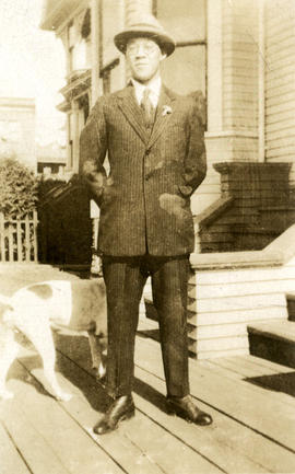 [Young man in suit standing in front of house]