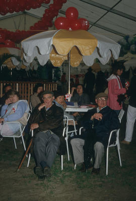 People seated under patio umbrella during the Centennial Commission's Canada Day celebrations