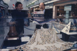 Unidentified man and Mike Harcourt standing behind display case