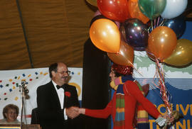 Mike Harcourt shaking hands with man in costume at Vancouver's 99th birthday celebration at the V...