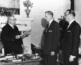 [The Honourable Frank Ross administers the oath of office to L.R. Peterson and Earle Westwood]