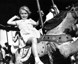 Child on merry-go-round in P.N.E. Gayway