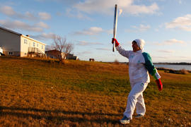 Day 24 Torchbearer 117 Cathy Williams carrying the flame in Lennox Island, Prince Edward Island.