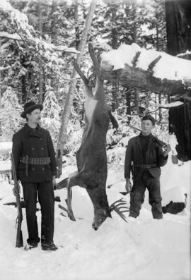 Two men with rifles posing with a hanging deer