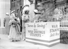 [Stoney Indians buying war savings stamps at a War Savings booth on the street]