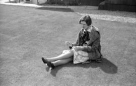 [Woman seated on lawn sewing the hem of her dress]