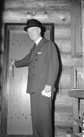 [Full length portrait of Premier John Hart at the door to the Hollyburn cabin]