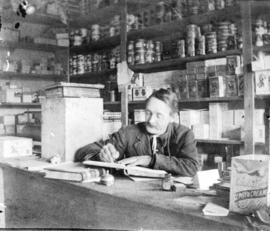 [Henry Ohlsen at work in his store near the boat landing on the San Josef River]