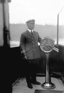 [Union Steamship Co. officer beside a telegraph on the ship's bridge]