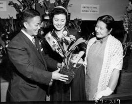 Miss P.N.E. and Chinese dignitaries with Flowers by Air exhibit in horticultural show, P.N.E. Forum