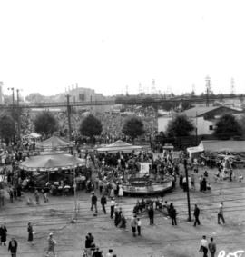 Crowd at Outdoor Theatre stage, with Home Arts building visible in background