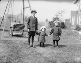 [Three children standing beside a swing in a yard]