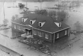 Building surrounded by flood waters and debris