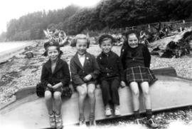 Children sitting on overturned boat at beach
