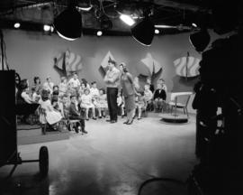 [Man and woman with a group of children on a television stage]
