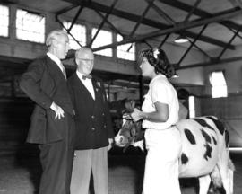 P.N.E. President J. S. C. Moffitt and unidentified man speaking with girl in Livestock building