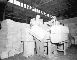 [Worker constructing crates for canned salmon]