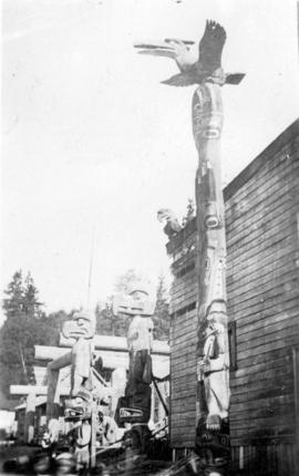 [Totem poles in front of longhouse]