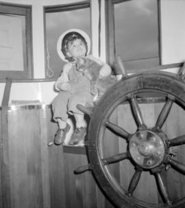 [Young girl holding a cat in the wheelhouse of a boat]