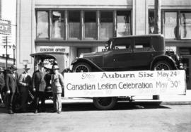 "Car on flatbed truck, banner reads ""This Auburn Six will be given away at the Canadian Legio..."