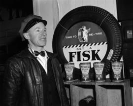 [B.A. Oil Company worker standing beside a Fisk tire and Peerless Motor Oil display]