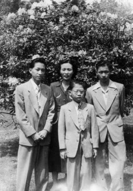 Mrs. Chan and her three sons in front of a rhododendron