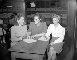 [Group of women sitting around a table writing in the switchboard room at B.C. Telephone]