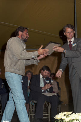 Gordon Campbell handing certificate to unidentified man at the lighting of the Peace Flame Monume...