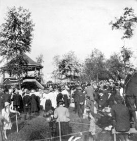 [A crowd around a decorated bandstand]