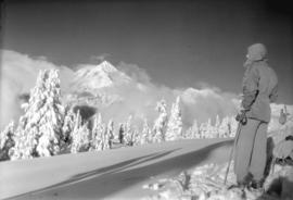 A skier looks towards Mount Garibaldi from the trail leading to Garibaldi Hostel's winter camp