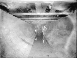 [Two men and one boy standing in partially constructed hydraulic tunnel from Buntzen Lake for Bun...