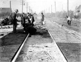 [Men laying bricks between railroad tracks on] Main St. - track construction