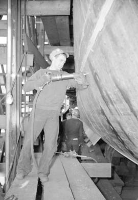 [Man with rivet gun working on boat at Burrard Drydocks]