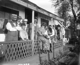 [People assembled on porch of James Stark's summer cottage at English Bay]
