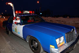 Day 73 Torchbearer 1 Gerald Walsh carries the flame in a RCMP vehicle in Regina, Saskatchewan.