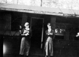 [Two women standing in front of the Seldom Inn at Summit Lake]