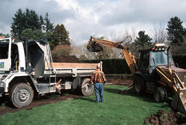 Backhoe digging soil and depositing it into Park Board truck