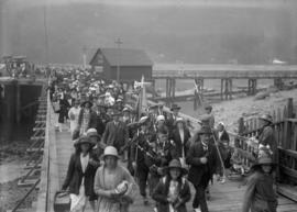 Crowd on a dock with a bagpiper