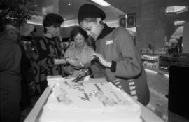 Unidentified woman serving cake at Legacies Program event at The Bay
