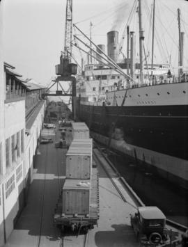 "[Crates of cargo on dock beside the ""Aorangi""]"