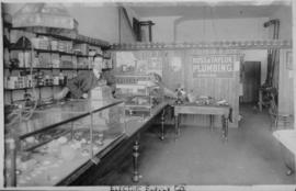 Roy Perry standing behind counter of the Electric Supply Company store located at 806 Robson Street
